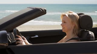 young woman driving convertible car by beach