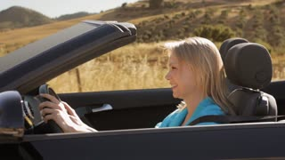 young woman driving convertible car in countryside