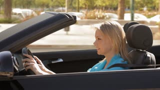 young woman driving convertible car in town