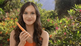 Young woman eating carrot in garden