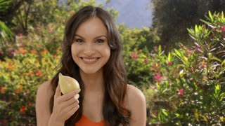 Young woman eating pear in garden