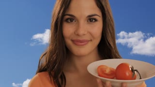 young woman eating tomato