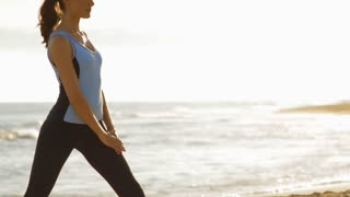 young woman exercising on the beach