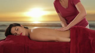 young woman having massage, sunset and beach background
