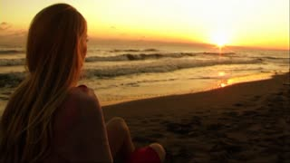 Young woman on beach watching sunset