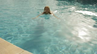 young woman swimming to side of pool