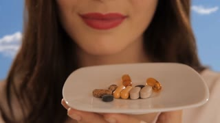 young woman with plate of vitamin pills