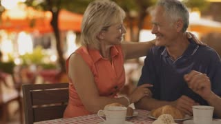 zoom in shot of senior couple at cafe in town