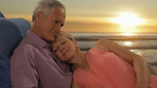 zoom in shot of senior couple relaxing by beach in sunset
