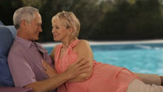 zoom in shot of senior couple relaxing by pool