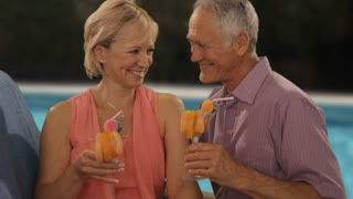 zoom in shot of senior couple relaxing by poolside with drinks