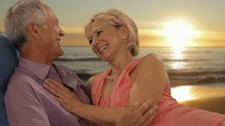 zoom in shot of senior couple relaxing by sea in sunset