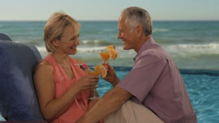 zoom in shot of senior couple relaxing by sea with drinks