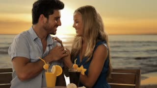 zoom in shot of young couple having drinks by sea in sunset