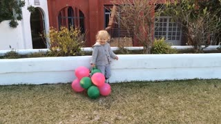Zoom in shot of young girl standing by wall with balloons