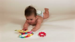 a baby laying on a white sheet playing with toys