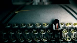 A tiny film noir style writer with pen and paper sitting on the keys of vintage 1940s typewriter writing a draft for his story.