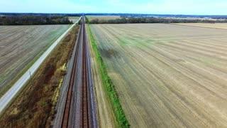 Aerial View Following A Train Track In Rural Farm Land