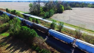 Aerial View Overlooking A Frieght Train Passing Rural Farm Land