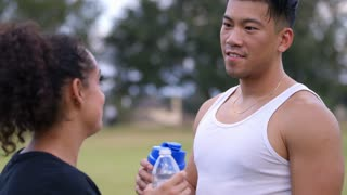 after exercising two people drinking water focus on man