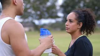 after exercising two people drinking water focus on woman