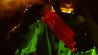 biohazard tech inspecting a vial of red liquid.