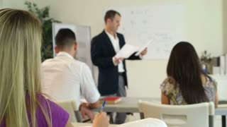 Blond student asks instructor question.