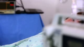 boy in hospital bed looks at camera dolly move