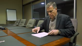 businessman at a corporate meeting room table going over paperwork 4k
