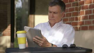 businessman at an outdoor cafe using a tablet pc.