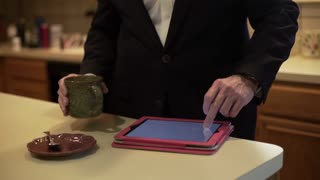 businessman drinking coffee and looking at tablet pc in kitchen 4k