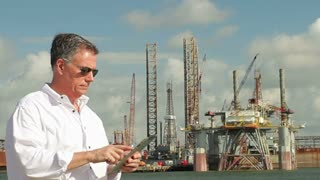 Businessman looking at tablet pc on a oil rig.