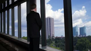 Businessman looking out of his office window smiles at camera.
