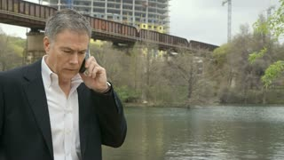 businessman on a cell phone next to a railroad bridge.