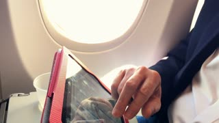 businessman on a passenger plane working with his tablet pc
