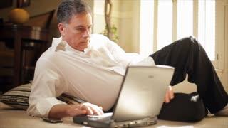 businessman on floor reading laptop