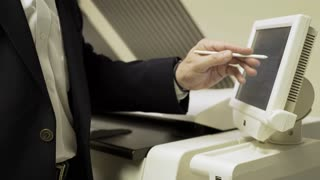 businessman pressing the touch screen of a large printer 4k
