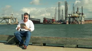 businessman sitting on a pier with oil platforms.