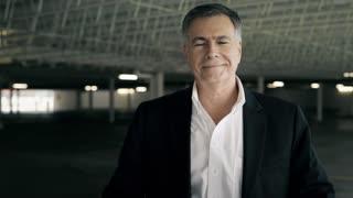 businessman standing in a parking garage smiles at camera 4k