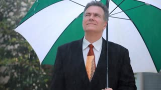 businessman standing under an umbrella in the rain