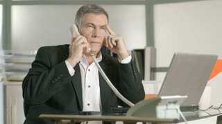 businessman taking care of two phone calls