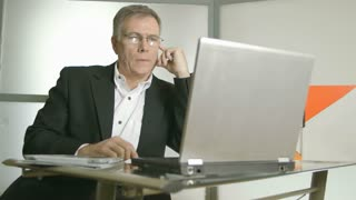 businessman typing on laptop and thinking