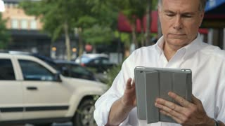 businessman using a tablet outside