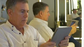 businessman using a tablet pc in front of an infinity mirror focus on person