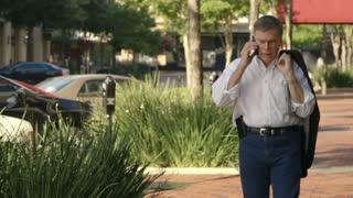 businessman walking down a sidewalk on the phone