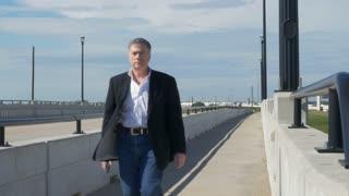 businessman walks past camera on bridge walkway 4k