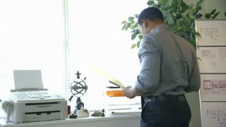 businessman walks to his desk and works