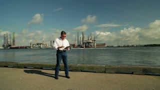 Businessman with a tablet pc in front of oil platforms.
