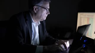 businessman working at night using a laptop in his office 4k