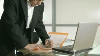businessman working on paperwork walks off